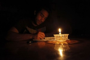 Mostafa Khaled, 20, studies by candlelight for his early morning exams during a power cut in Toukh, El-Kalubia governorate, about 25 km (16 miles) northeast of Cairo May 26, 2013. The Egyptian government said on Wednesday it would supply more gas and diesel to power stations to deal with electricity shortages that have worsened in recent months after the cash-strapped country failed to import enough fuel. Picture taken May 26, 2013. REUTERS/Amr Abdallah Dalsh (EGYPT - Tags: EDUCATION BUSINESS ENERGY)